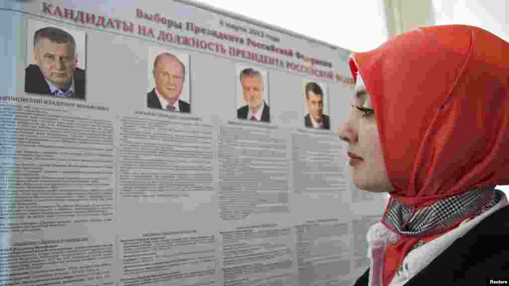 A woman looks at a list of presidential candidates at a polling station in Grozny, Chechnya