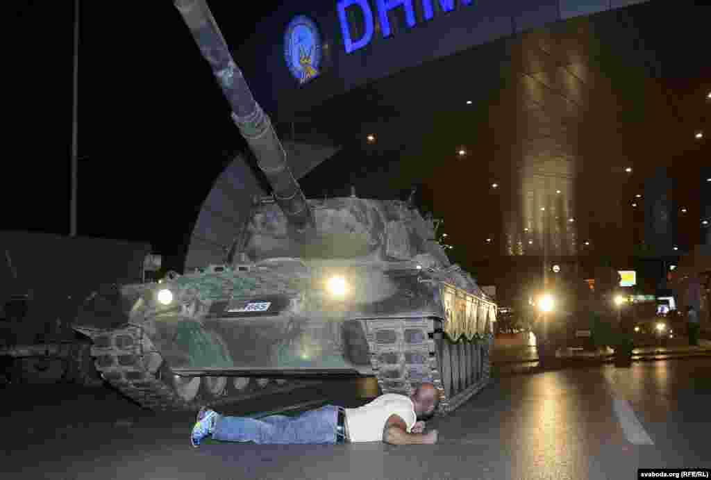 "A man lies in front of a Turkish Army tank at Ataturk airport in Istanbul. As flights were suspended, Turkish Airlines took to Twitter to condemn the attempted coup, saying, ""Citizens who believe in democracy and freedom to stand up against this attack on our Parliament and our public representatives."""