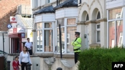 A police officer stands on duty outside a residential property in Manchester as investigations continue into a deadly bomb attack earlier this week.