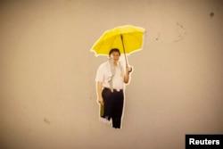 """Фотоколлаж китайского лидера Си Цзиньпина с желтым зонтиком был оставлен демонстрантами на стене в гонконгском районе """"Адмиралтейство"""" в 2014 году."""