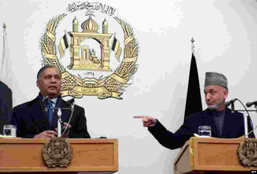 Afghan President Hamid Karzai gestures toward visiting Pakistani Prime Minister Shaukat Aziz in January 2007 - Afghan officials first suggested that insurgents or terrorists were crossing over from Pakistan in 2003, triggering an attack on Pakistan's embassy by an angry mob. Relations have run hot and cold ever since.