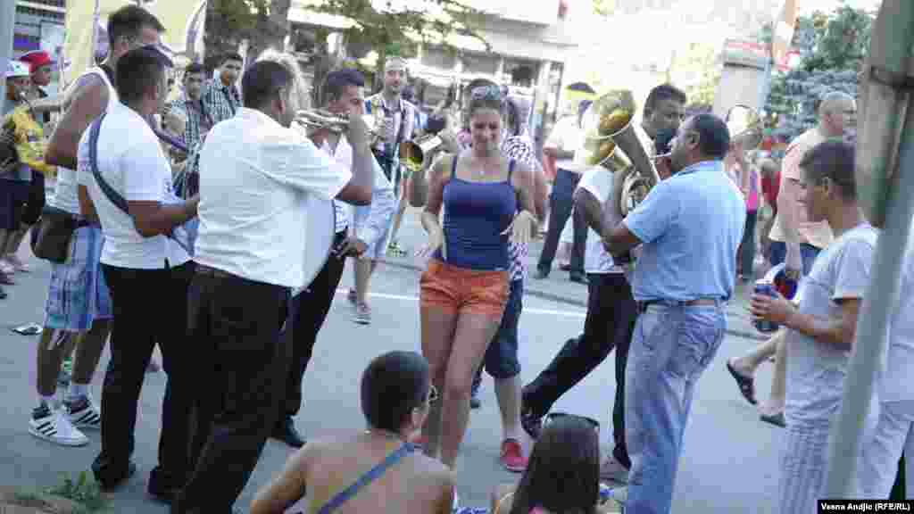 A young woman dances to the music of a Roma brass band.