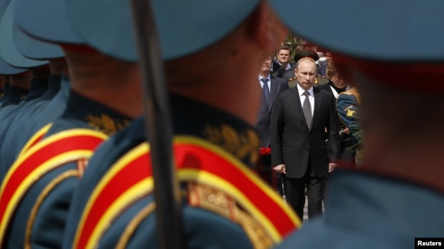 President Vladimir Putin is seen past Russian soldiers at a ceremony at the Tomb of the Unknown Soldier in Moscow in 2012.