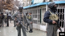 Afghan security officials inspect the scene of a suicide bomb attack in Kabul on February 26