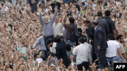 Mir Hossein Musavi (center) raises his arms as he appears at a massive opposition demonstration in Tehran on June 15.