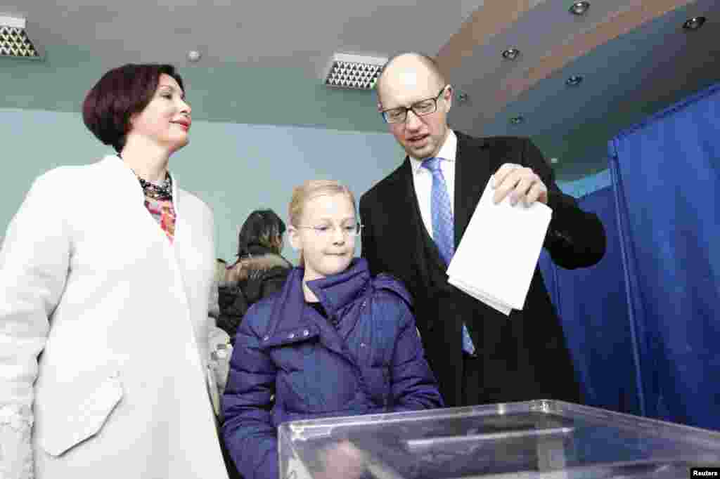 Ukraine's Prime Minister Arseniy Yatsenyuk (right) casts his ballot, as his daughter Sofiya (center) and wife Teresiya stand nearby, during parliamentary elections at a polling station in Kyiv on October 26. (Reuters/Gleb Garanich)