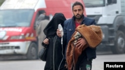 A man carries a child with an IV drip as he flees deeper into the remaining rebel-held areas of Aleppo on December 12.