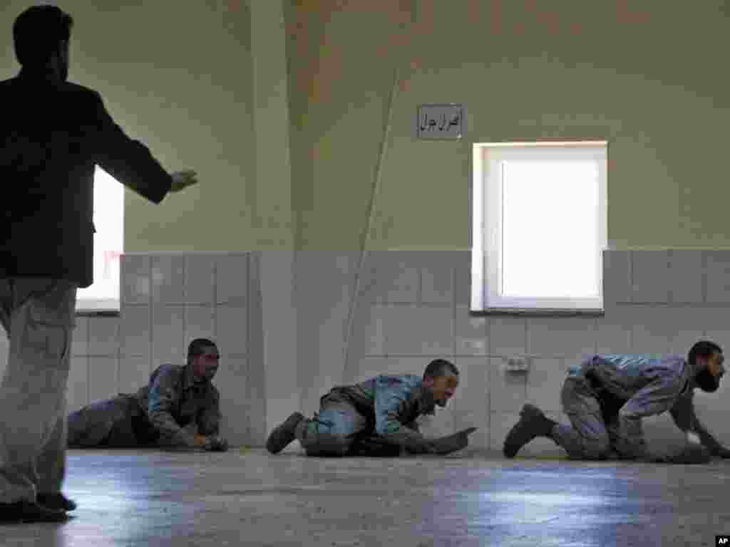 Afghan police officers duck for cover after a mortar hit the compound of the National Police Training Center during an inauguration ceremony in central Wardak Province on June 15.Photo by Gemunu Amarasinghe for AP