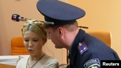 An Interior Ministry officer asks ex-Prime Minister Yulia Tymoshenko (left) to be quiet during a session at the Pechera district court in Kyiv in October 2011.