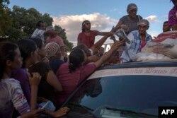 Беженцы из Венесуэлы возле машины с гуманитарной помощью с бразильской стороны общей границы. Октябрь 2018 года