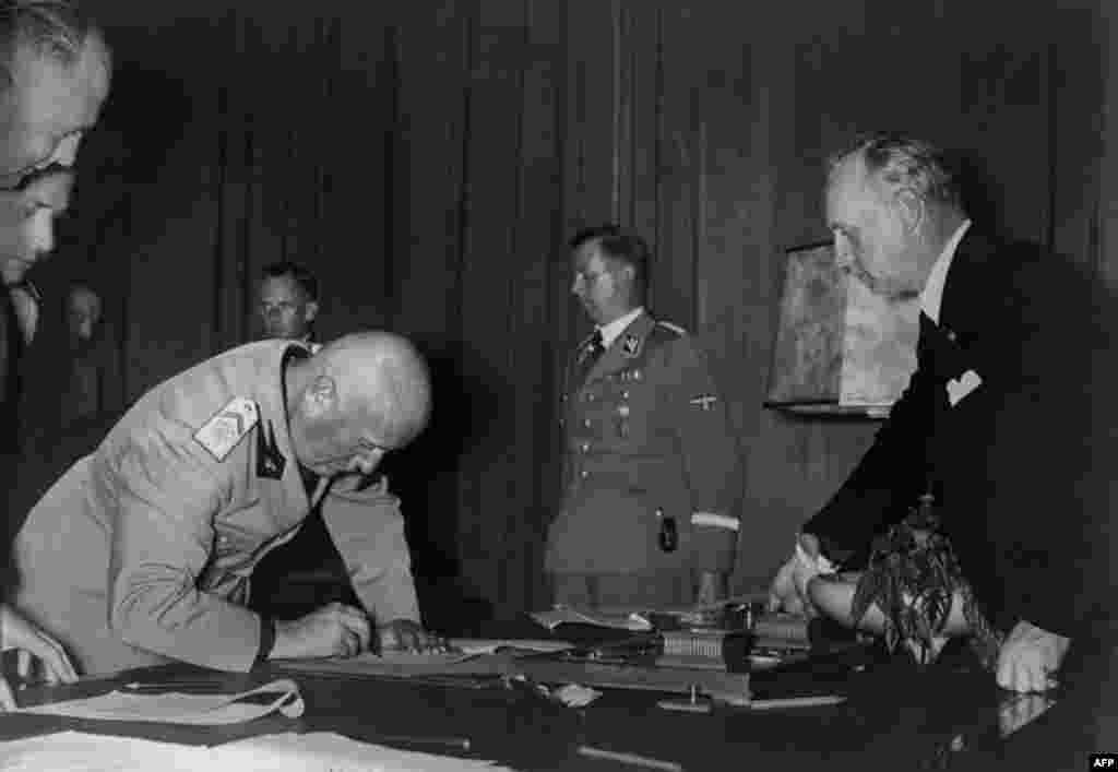 Italian Prime Minister Benito Mussolini signs the Munich Agreement as Martin Bormann (second right) and Joachim von Ribbentrop (right) look on.