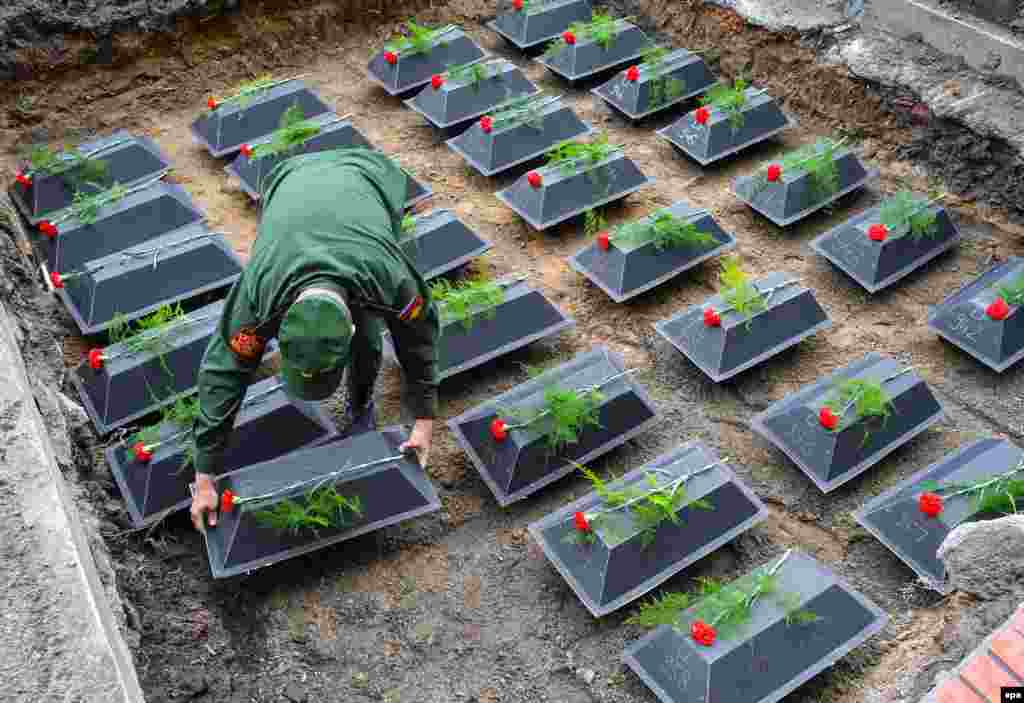 A Russian soldier places small coffins containing the remains of Soviet troops from World War II at the military cemetery in Lebus, Germany, on August 18. (epa/Patrick Pleul)