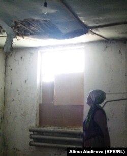 Ардак Кубашева показывает аварийную крышу Дома культуры. Село Шубарши, 11 июля 2011 года.