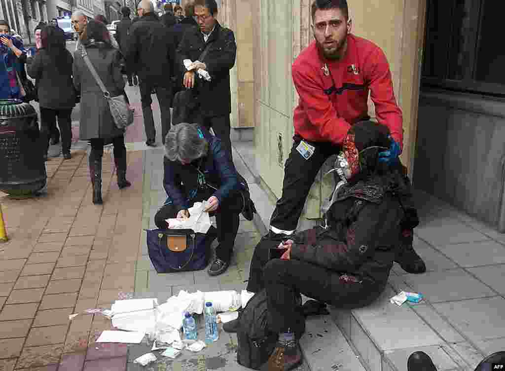 A private security guard helps a wounded woman outside the Maalbeek metro station in Brussels after a terrorist attack claimed by Islamic State on March 22. (AFP/Michael Villa)