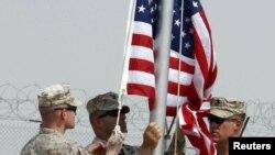 Солдаты снимают флаг США во время церемонии передачи власти на военной базе США в Басре, 11 июля 2010
