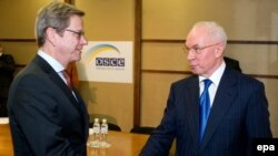 German acting Foreign Minister Guido Westerwelle (left) greets Ukrainian Prime Minister Mykola Azarov during the OSCE meeting in Kyiv on December 5.