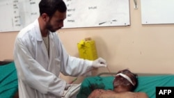 A wounded man receives treatment from a doctor at a hospital in Kandahar following the blast.