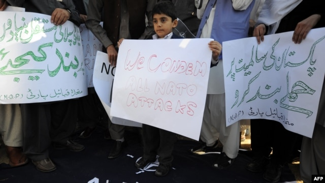 Pakistani tribesmen stand on a NATO flag during a demonstration against the strikes on Pakistani troops in Islamabad.