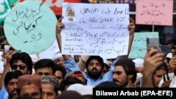 FILE: People shout slogans during a protest to support Khalid Khan, the man who allegedly killed Tahir Nasim, a man accused of blasphemy inside a court in the northwestern city of Peshawar on July 31.