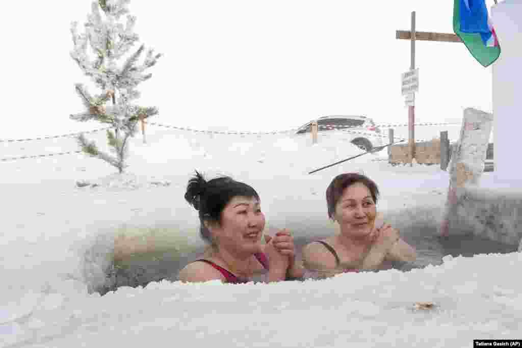 Жінки купаються в річці Лена, коли температура впала приблизно до мінус 56 градусів за Цельсієм в Якутську, Росія