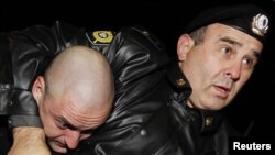 A police officer detains Sergei Udaltsov (left), leader of the Left Front organization, during the October 12 protest in Moscow.