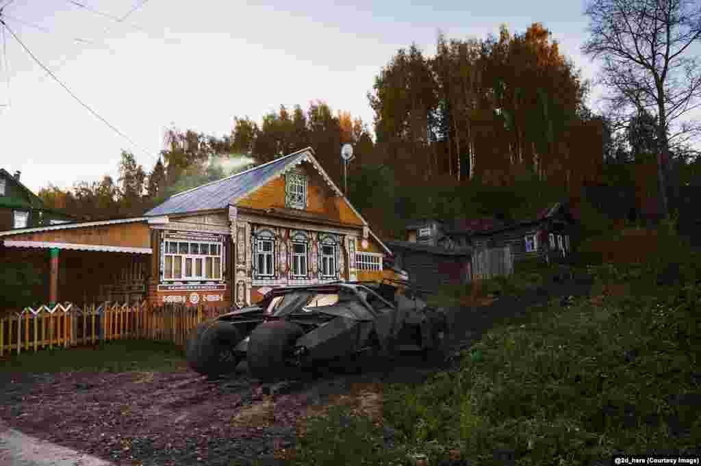 Batman's tumbler batmobile parked outside a dacha.