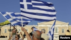 A man holds a Greek flag before a conservative New Democracy party rally on Syntagma Square in Athens on June 15.