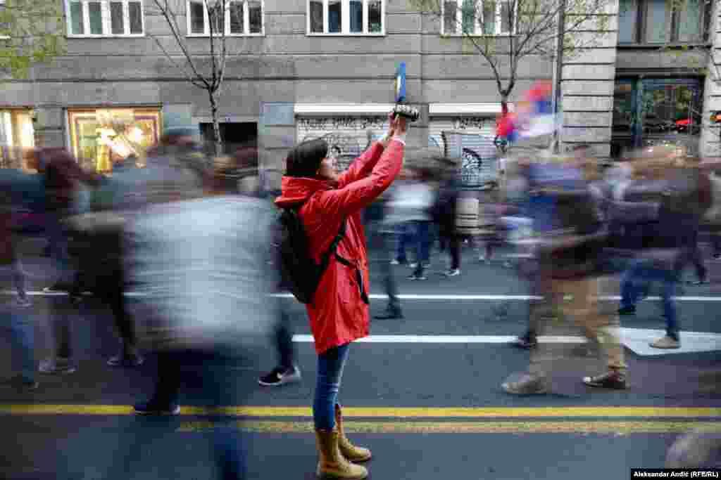 Женщина снимает протестующих во время антиправительственных акций «Один из пяти миллионов» в Белграде 6 апреля 2019 года. (Aleksandar Anđic, RFE/RL)