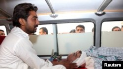 The brother of Ansar Iqbal sits in an ambulance next his brother's bodyafter his execution.