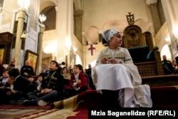 O fata așezată în Categrala Sfânta Treime din Tbilisi, Georgia, în timpu Slujbei de Bobotează, 19 ianuarie (Mzia Saganelidze, RFE/RL)