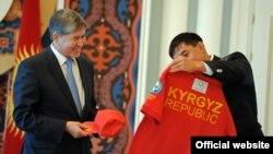 Капитан национальной олимпийской команды КР борец Данияр Кобонов вручил президенту КР Алмазбеку Атамбаеву памятную кепку и футболку с олимпийской символикой, Бишкек, 16 июля