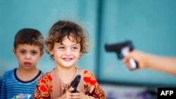 صورة من الأرشيف لأطفال عراقيين نازحين من الموصل وهم يلعبون ألعاب مسدسات