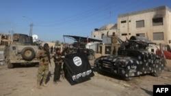 Իրաքի զինված ուժերի զինծառայողները ազատագրված Ռամադիում տոնում են հաղթանակը՝ ցույց տալով պարտված «Իսլամական պետության» դրոշը, 28-ը դեկտեմբերի, 2015թ․