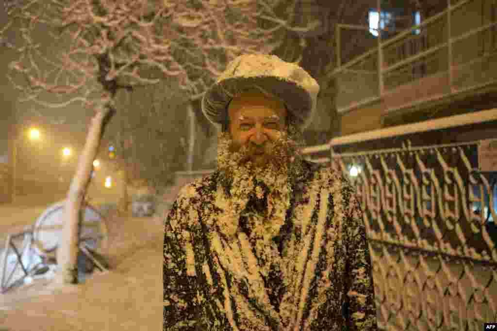 An ultra-Orthodox Jewish man covered with snow walks in Jerusalem. Jerusalem was transformed into a winter wonderland after heavy snowfall turned the Holy City and much of the region white, bringing hordes of excited children onto the streets. (AFP/Menahem Kahana)