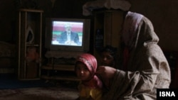 An Iranian woman and her child watch one of the three televised presidential debates in early June.