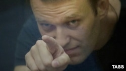 Russian opposition leader Aleksei Navalny gestures inside a glass-walled cage during his court hearing in Kirov on July 19