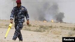 Өрт шыққан мұнай құбыры маңын тексеріп жүрген полицей. Ирак, 10 мамыр 2010 жыл.