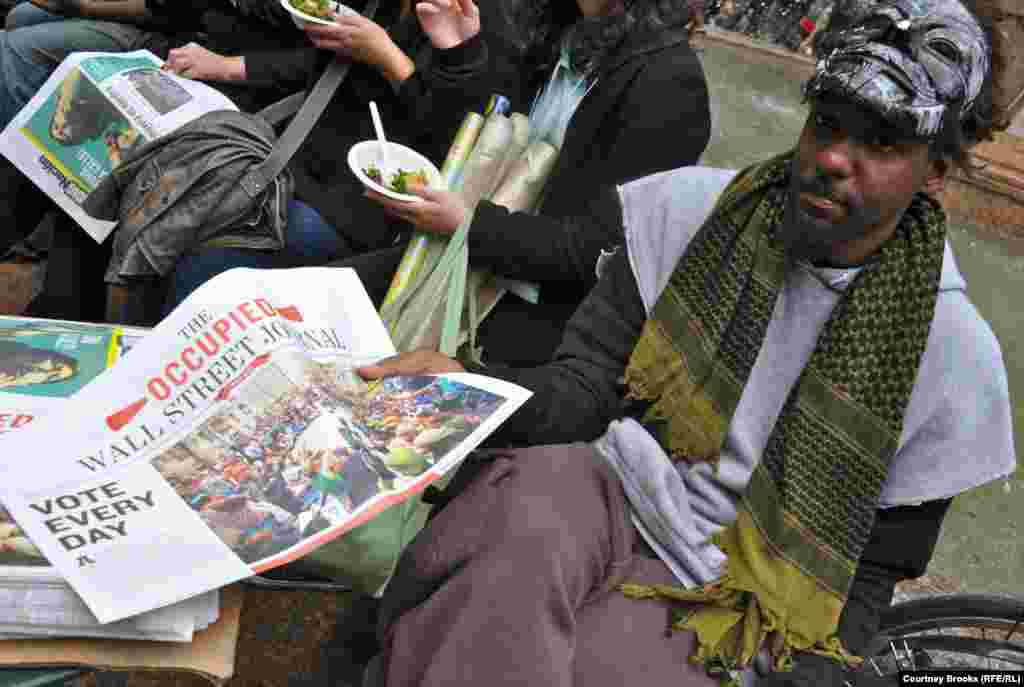 "A protester hands out copies of the movement's newsletter, ""The Occupied Wall Street Journal,"" in New York City's Bryant Park."