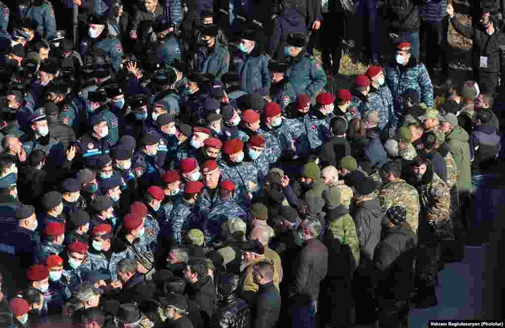 Ерменската полиција е на стража додека Пашинијан оддава почит на воените гробишта на 19 декември.