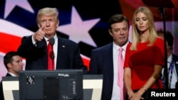 Then-Republican presidential nominee Donald Trump gives a thumbs-up as his then-campaign manager, Paul Manafort (center), and daughter Ivanka look on at the Republican National Convention in Cleveland on July 21.