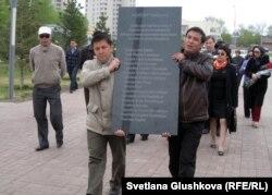 Гражданские активисты несут мемориальную плиту в память погибших в Жанаозене. Астана, 28 апреля 2012 года.