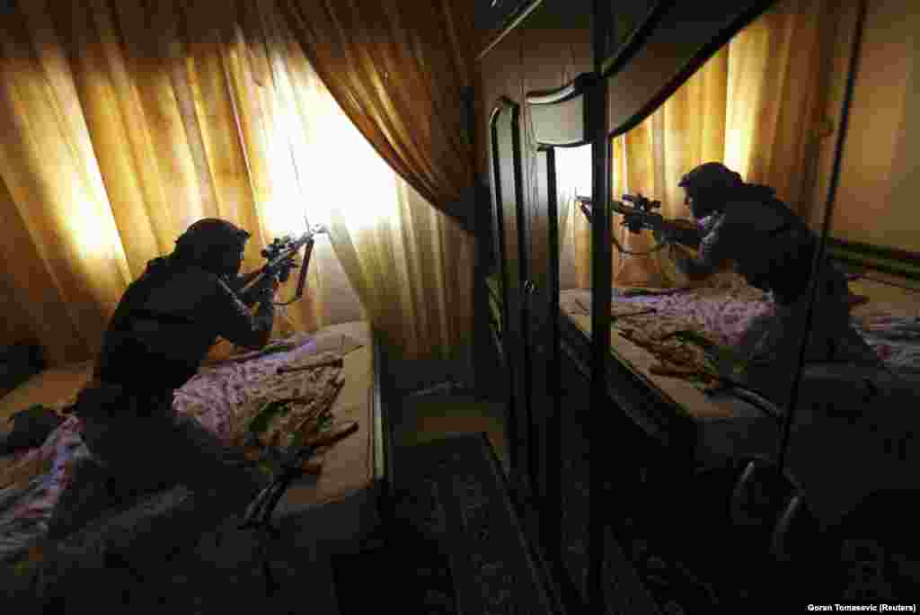 A fighter from the Free Syrian Army fires his sniper rifle from inside a house during heavy fighting in the Mleha suburb of Damascus. (Reuters/Goran Tomasevic)