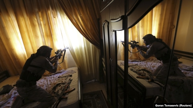 A fighter from the Free Syrian Army fires his sniper rifle from inside a house during heavy fighting in a suburb of Damascus.