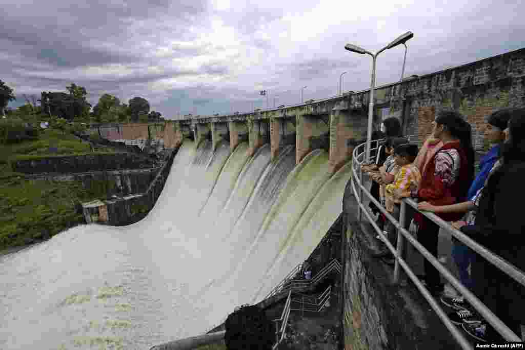 People watch at the Rawal Dam after the spillway opened due to heavy monsoon rains in Islamabad on August 31. More than 100 Pakistanis died in August because of the monsoon, which also destroyed more than 1,000 homes. (AFP/Aamir Qureshi)