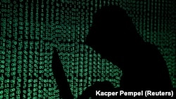 ILLUSTRATION -- FILE PHOTO: A hooded man holds a laptop computer as cyber code is projected on him in this illustration picture taken on May 13, 2017.