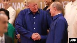 Дональд Трамп пен Владимир Путин қол алысып тұр.