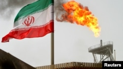 FILE PHOTO: A gas flare on an oil production platform is seen alongside an Iranian flag in the Gulf July 25, 2005.
