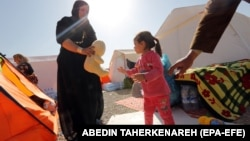 یک مادر و کودک در کنار چادرهای اسکان موقت در سرپلذهاب