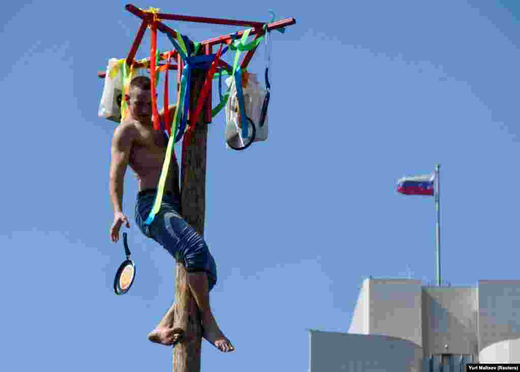 A man drops a skillet, which he received as a prize, after he climbed up a wooden pole in Russia's Far Eastern city of Vladivostok.