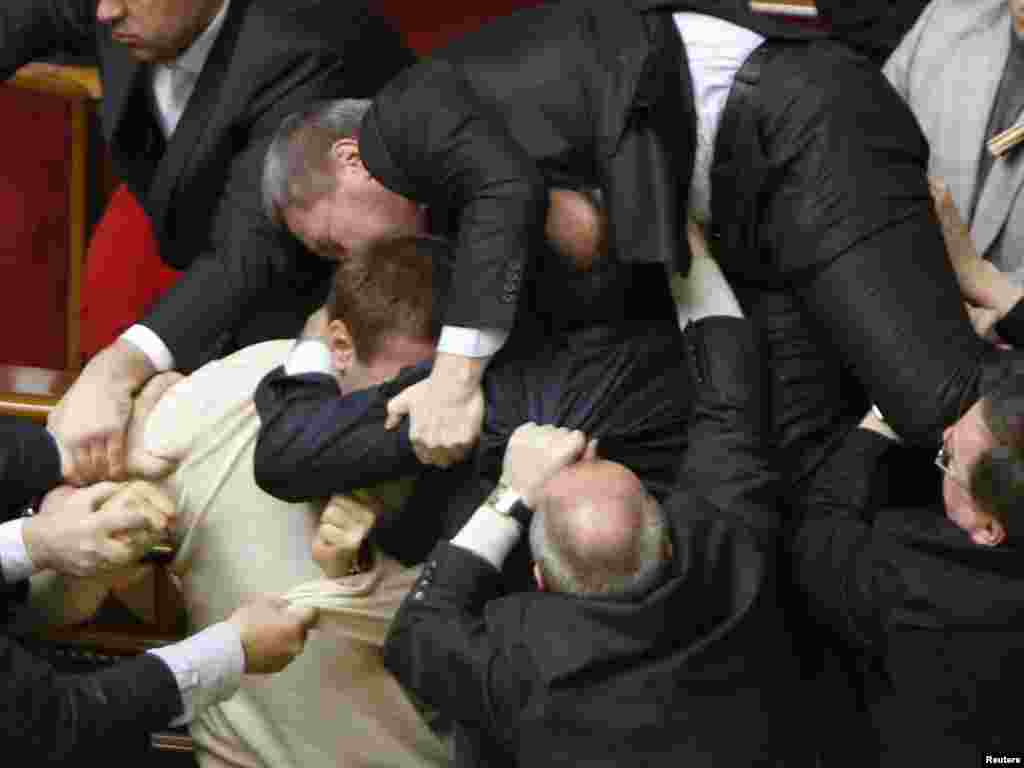 Ukrainian lawmakers brawl in parliament after the chamber approved a divisive deal allowing the Russian Navy to extend its stay on Ukrainian territory. Chaos erupted as opposition deputies threw eggs and smoke bombs. Photo by Gleb Garanich for Reuters